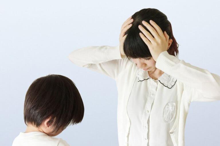 叱られている子どもと 頭を抱える母親